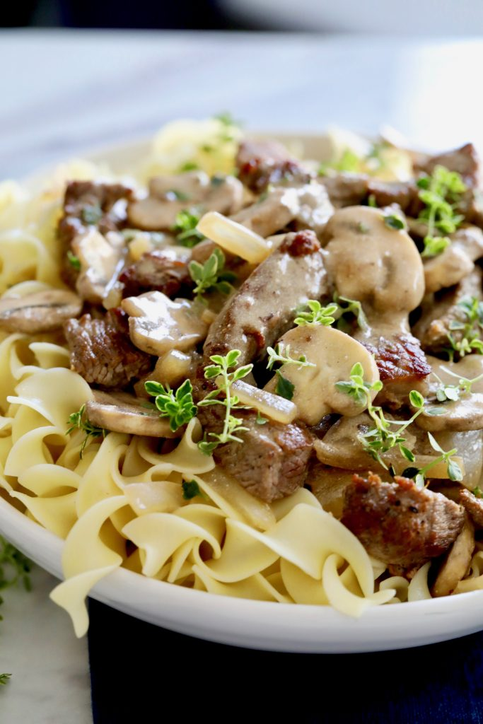 A white bowl of wide egg noodles topped with Beef Stroganoff using pieces of browned Tri-Tip Steak and Mushrooms, covered in rich stroganoff sauce and garnished with thyme sprigs.